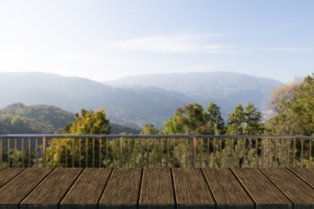 banister: metal banister of balcony with mountain view (blur background with wood table top for display or montage your product) Stock Photo