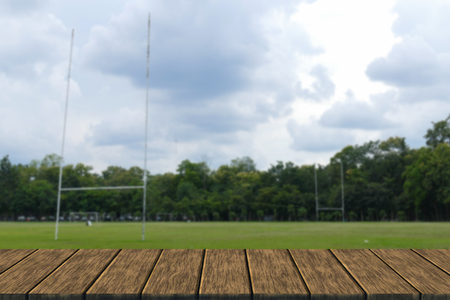 goal of rugby field in the park (blur background with wood table top for display or montage your product) Reklamní fotografie - 54485308
