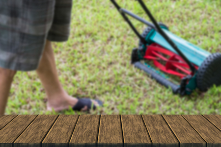 mow: man using lawn mower to mow grass (blur background with wood table top for display or montage your product)