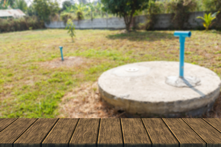 septic tank: underground cement cylinder of lavatory cesspit in lawn yard (blur background with wood table top for display or montage your product)