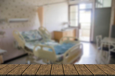 private room: empty bed for patient in private room (blur background with wood table top for display or montage your product)
