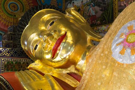 smiling buddha: smiling face of reclining golden buddha statue in asian temple