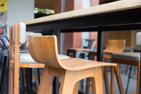 stool: brown wooden table with stool at patio of building
