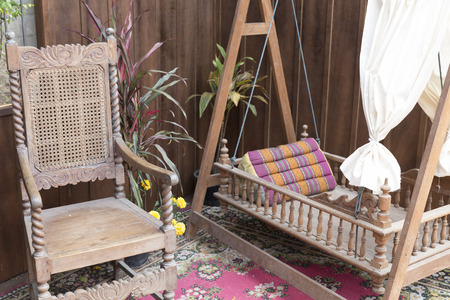 old furniture: antique wooden chair and traditional cradle at patio