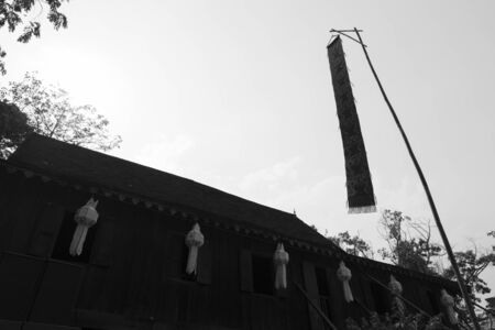lanna: white lanna paper lantern decorating  on wooden ancient lanna house and lanna flag, black and white