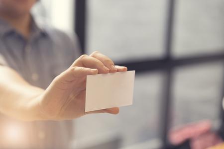 Vrouwelijke hand die blanco witte naamkaart, selectieve focus en vintage toon bevat