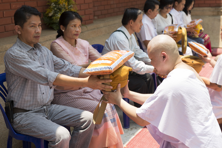 monk robe: Chiang Mai, Thailand - April 30, 2016: man receive monk robe from their parent in buddhist monk ordination ceremony at Umong temple in Chiang Mai, Thailand on April 30, 2016. Editorial