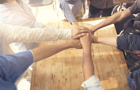 mensen zetten hun handen in elkaar voor United, samenwerking en teamwork concept, selectieve aandacht en vintage toon