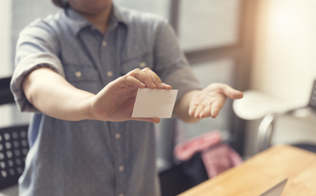 identification: womans hand holding blank white name card, selective focus and vintage tone