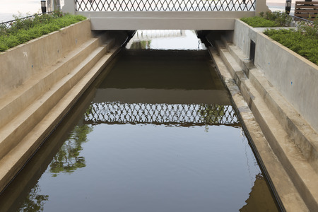 across: pedestrian footbridge across small canal in park Stock Photo