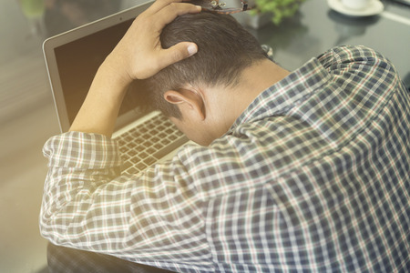 frustrate: mans head on laptop computer for frustrate and stress concept, selective focus and vintage tone Stock Photo