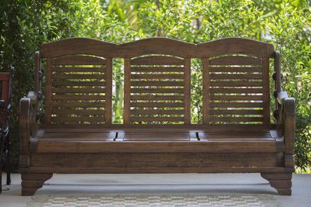porch scene: brown wooden bench for resting in garden