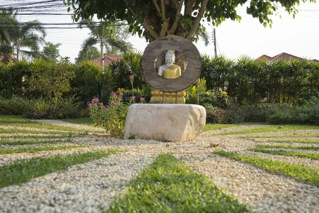 Robe: meditating silver buddha statue with golden robe in garden