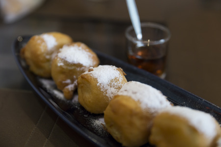 dessert topping: fried banana dessert topping with icing sugar on black dish serving with honey, selective focus