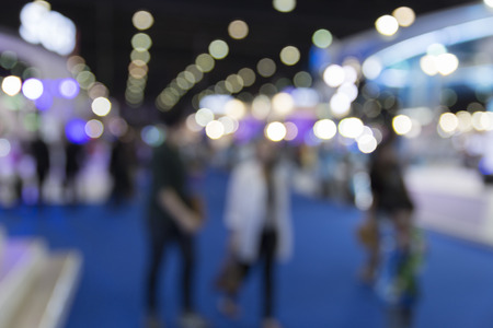 people in tradeshow exhibition hall building, blur background
