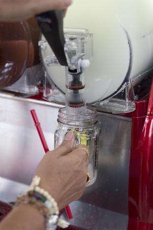 granizados: hand pulling cold ice slush fruit juice beverage equipment machine, selective focus