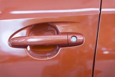 automobile door: door handle of new orange car automobile, selective focus Stock Photo