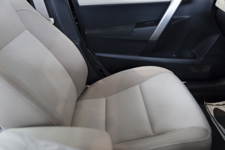 safty: new brown fabric passenger seat and safty belt in car, selective focus