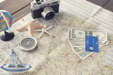 compass, credit card, banknote money, globe, camera, map, ship and starfish figurine on wooden table for use as traveling concept (vintage tone and selected focus)