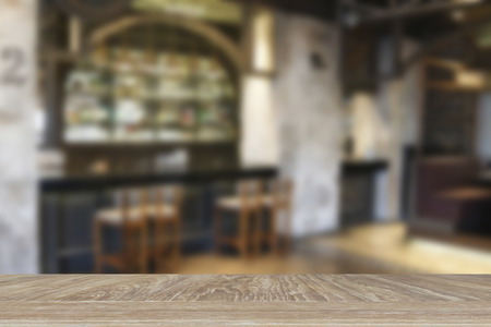 beverage display: wooden table for display or montage your product with blur background of glasses and bottle of alcohol beverage at counter bar Stock Photo