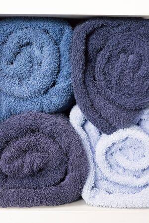 white shelf: pile of rolling blue towel on white shelf