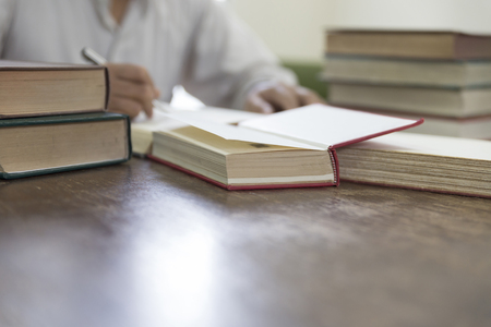man reading book with textbook stack on wooden desk in library Stock Photo