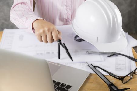 architect hand holding compass working on construction engineering project blueprint Stock Photo
