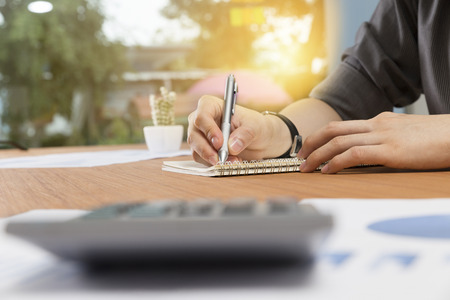 writing desk: businessman writing note on notepad on office desk Stock Photo