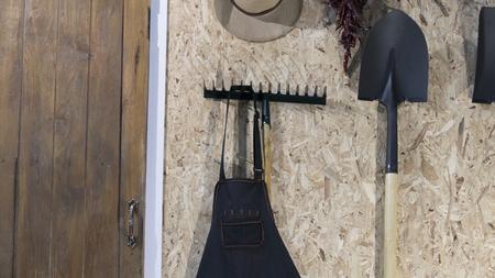 harrow: hoe, shovel spade, harrow and hat beside wooden door Stock Photo