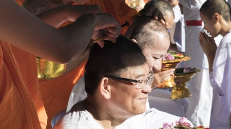 become: Lampang, Thailand - July 18, 2016: monk shave hair of man who will become buddhism monk in ordination ceremony at Bunyanupab temple in Lampang, Thailand on July 18, 2016.