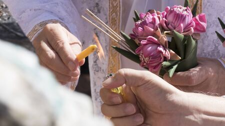 temple burn: people holding pink lotus and lighting candle in buddhism monk ordination ceremony