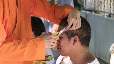 ordination: Lampang, Thailand - July 18, 2016: monk cut hair of man who will become buddhism monk in ordination ceremony at Bunyanupab temple in Lampang, Thailand on July 18, 2016. Editorial