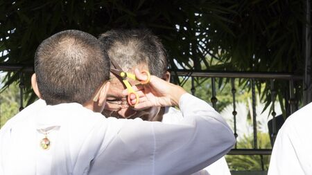 ordination: Lampang, Thailand - July 18, 2016: people cut hair of man who will become buddhism monk in ordination ceremony at Bunyanupab temple in Lampang, Thailand on July 18, 2016.