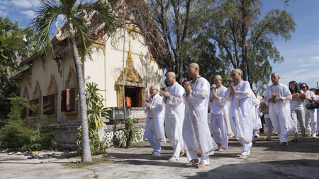 relatives: Lampang, Thailand - July 18, 2016: man who will become buddhism monk praying and walking around church with their relatives in procession in ordination ceremony at Donchai temple in Lampang, Thailand on July 18, 2016.