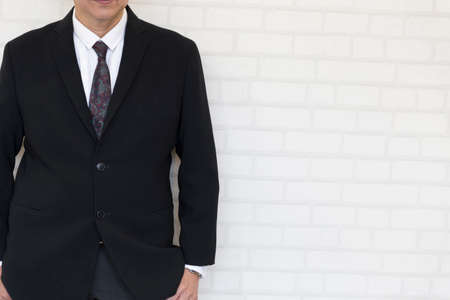 hand in pocket: businessman hand in pocket standing beside white wall