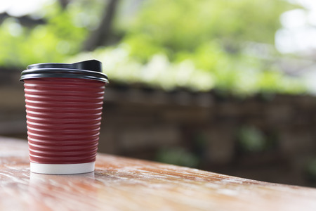 cappuccino cup: hot cappuccino coffee in red paper cup on wooden table with green leaves background