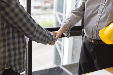 architect engineer shaking hands beside window - business teamwork, cooperation, success collaboration concept Stock Photo - 63231031