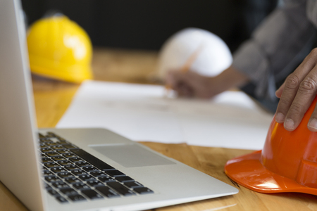 construction project: architect holding pencil working on blueprint of construction project in workplace with computer on office desk