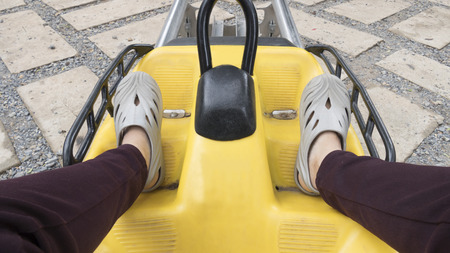 thrill: leg of woman sitting on yellow roller coaster