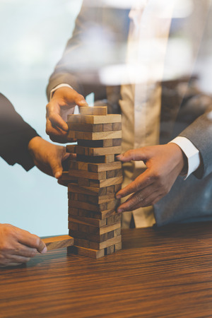 planning strategy: planning, risk and strategy in business, businessman gambling placing wooden block on a tower Stock Photo