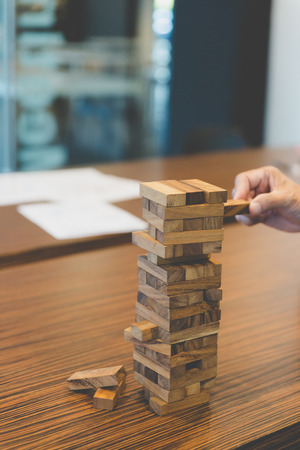 planning, risk and strategy in business, businessman gambling placing wooden block on a tower Stock Photo