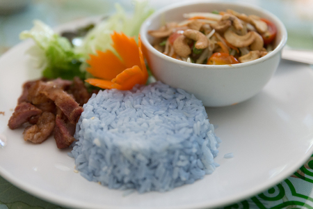 blue rice, fried pork and papaya salad or somtum Stock Photo