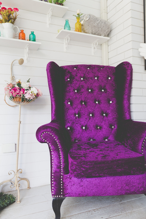 old style retro vintage purple velvet armchair and flower bouquet beside white wood wall Stock Photo