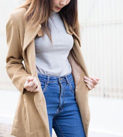 かなり若いアジアの女の子女性ブルー ジーンズとの建物の近くの茶色のジャケットを着て 写真素材