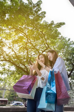 two happy asian shopaholic women with smartphone and colorful shopping bags at park Stock Photo
