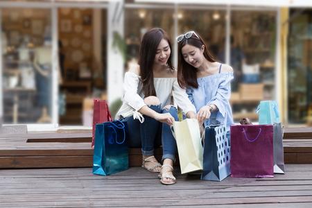 twee gelukkige Aziatische shopaholic vrouwen met kleurrijke boodschappentassen bij warenhuiswinkelcomplex Stockfoto