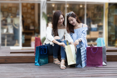 two happy asian shopaholic women with colorful shopping bags at department store shopping mall