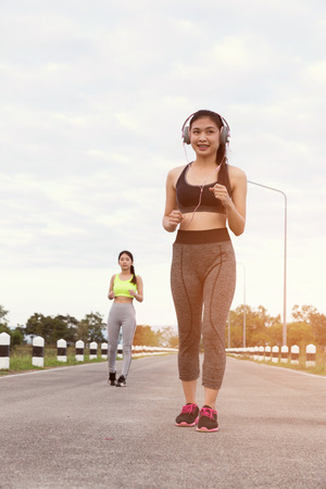 spandex: Young sporty woman jogging, running at the park Stock Photo