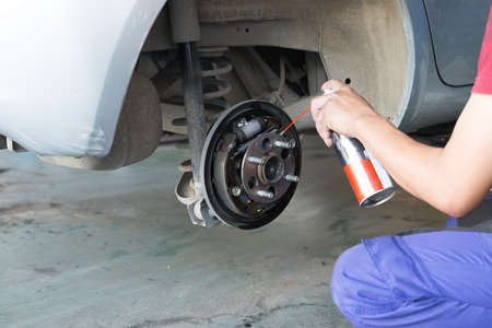 mechanic spray chemical to clean brake during tyre replacement service