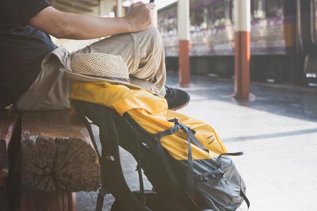 Reiziger man met een rugzak zitten en wachten op de trein op het station. Outdoor avontuurlijke reizen per trein concept Stockfoto